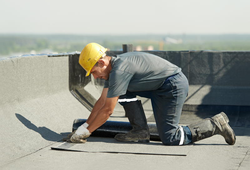 man working on a flat roof in portland oregon