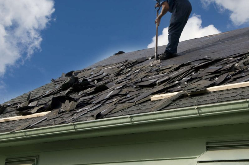 Removing old shingles to prepare a roof for a new installation with winter sky